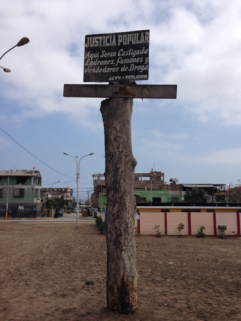 "A sign on a cross located in Sector 2, Group 18 of the Villa El Salvador district in Lima warns, ""Popular Justice: Thieves, Stoners, and Drug Dealers Will Be Punished Here."" Photo by Steven T. Zech."