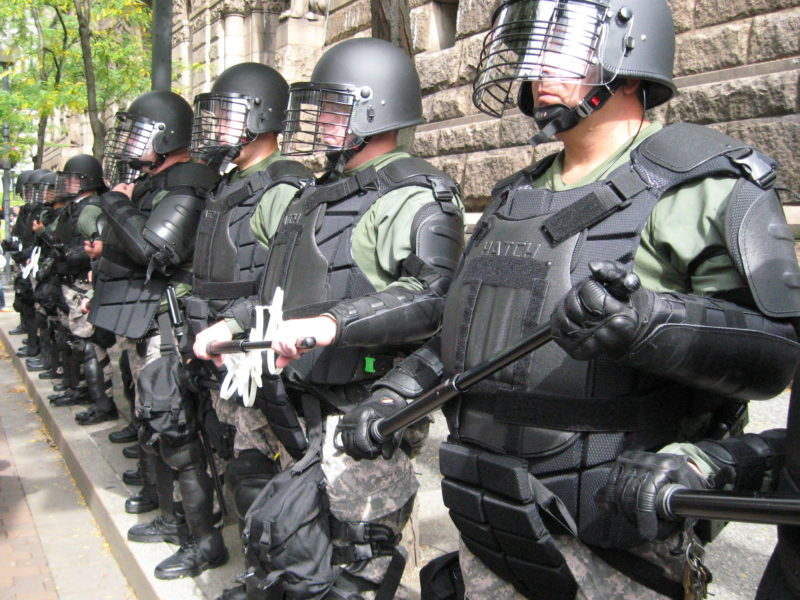 Line of police officers with batons and camo. Photo courtesy of katesheets.